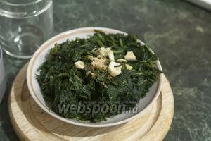 В размороженный отжатый шпинат добавляем кусочки очищенного чеснока и порошок имбиря (можно заменить 1 см свежего корня имбиря).
