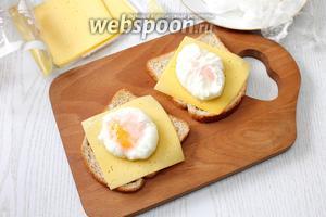 Тостовый хлеб поджарьте в тостере. На хлеб по желанию уложите ломтики сыра или мясной нарезки. Из пакетиков аккуратно достаньте яйца, уложите каждое на тост.