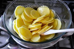 Как только масло полностью растает, выложить в миску картофель и осторожно перемешать, чтобы не поломать его.