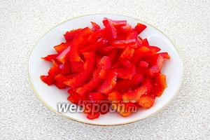Плод сладкого перца вымыть, удалить плодоножку и семяносцы с семенами, а затем разрезать вдоль на 4 части и каждую 1/4 нашинковать тонкой соломкой.