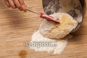 Затем получившееся тесто выкладываем на чистую столешницу в горку муки.