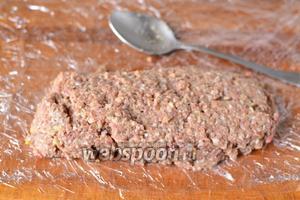 Теперь самое время придать колбасе форму. Пищевую плёнку разворачиваем на доске, я делаю это в несколько слоёв. Вместо пищевой плёнки можно использовать рукав для выпечки. Выкладываем часть фарша на плёнку и формируем колбаску. Из всего фарша колбаса будет слишком толстая и не проварится.