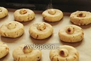 От теста отрывать кусочки размером с орех, сформировать в шарик, а сверху положить по фундуку. Выпекать при температуре 200ºC 15-20 минут.