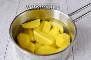 Картофель очищаем, тщательно моем и нарезаем большими ломтиками. Для этого рецепта лучше брать такие сорта, которые легко варятся и являются более крахмалистыми. Бросаем картофель в большую кастрюлю и заливаем его холодной водой. Её берём примерно 1 литр. В идеальном варианте, вода должна полностью покрывать картофель, но в то же время её не должно быть чересчур много. Кастрюлю с водой ставим на большой огонь и дожидаемся её закипания. После этого огонь следует уменьшить и варить картошку до полной её готовности. За 10 минут до окончания готовки солим нашу картошку. Количество соли берётся на ваше усмотрение.