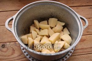 К обжаренному мясу добавьте сырой картофель. Залейте водой и тушите около 20 минут.