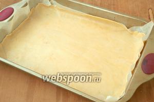 Вложить тесто в форму, обрезать так, чтоб получились бортики. Обрезки теста можно использовать для декора.