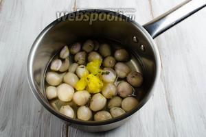 Надрезать в корневой части луковицы крест-накрест, чтобы при варке они не лопались. Сложить подготовленные луковички в сотейник. Залить их водой так, чтобы слой воды прикрыл их наполовину. Положить в сотейник топлёное масло, соль, тимьян. Накрыть крышкой. Довести до кипения. Томить минут 20-30 на медленном огне. Отбросить луковицы на дуршлаг. Бульон луковый не выливать!