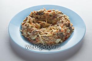 На той тарелке, на которой собираемся сервировать салат, формируем вот такое вот гнездо с высокими бортиками и глубоким центром из основной массы салата.