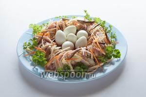 Посыпаем салат всеми полосками, припасёнными для декора, втыкаем декоративно петрушку, и декорируем центр гнезда перепелиными яйцами. Готово!