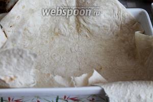 В форму для запекания, смазанную маслом, уложить лепёшку, чтобы края свисали.