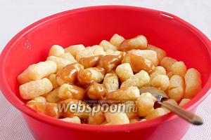 Сразу же, пока смесь ещё горячая, нужно постепенно лить её в миску с кукурузными палочками и быстро размешивать. Палочки добавлять по мере размешивания основной массы. Не оставляйте ирисковую смесь без палочек, она быстро застывает.