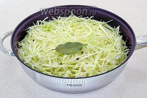 Капусту нашинковать тонкой соломкой, выложить в глубокую сковороду, влить 2/3 стакана воды, положить 1 ст. л. масла, перец и лавровый лист.