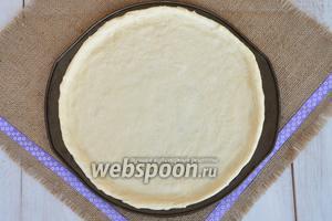 Тесто вынуть из хлебопечи, обмять и разделить на 2 части. Из этого количества продуктов получится 2 пиццы диаметром 33 см. Растянуть руками в круг и разровнять на форме для пиццы. Форму предварительно смазать растительным маслом.