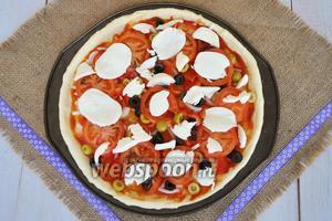 Моцареллу нарезать или поломать руками и разложить по поверхности пиццы.