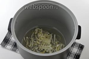 В чашу мультиварки выложить подсолнечное масло и нарезанный тонкими полосками лук.