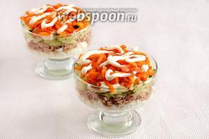Потом черёд огурцов и моркови. Огурцы отжать от лишней жидкости. На каждый слой нанести сеточку из майонеза.