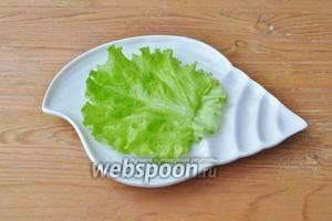 На порционную тарелку положить лист салата.