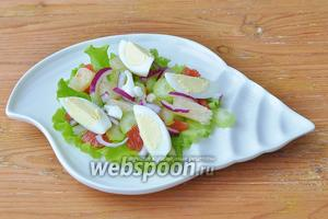 Яйцо разрезать на 4 части и выложить на тарелку. Добавить немного синего лука.