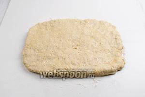 Выложить тесто на подпыленную мукой рабочую поверхность стола. Растянуть тесто толщиной 3 см в прямоугольник. Причём, ширина должна быть равной длине формы для выпечки.