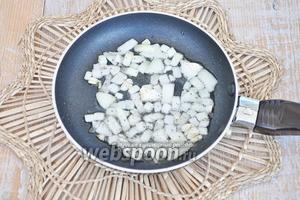 На порциооную сковородку налить немного масла и обжарить лук до прозрачности, добавить перец.