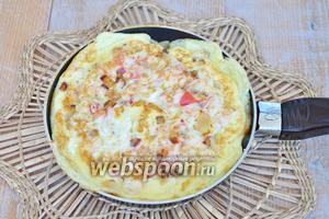 Влить яйца и обжарить омлет с двух сторон до готовности.