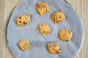 Застелите противень пекарской бумагой и столовой ложкой выложите на него небольшие горки теста на расстоянии 3-5 см друг от друга. Из указанного количества ингредиентов получится около 20 печений. Духовку разогрейте до 200°С.