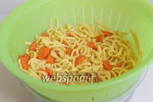 Отвариваем лапшу, в конце добавляем морковь. Откидывaем на дуршлаг.