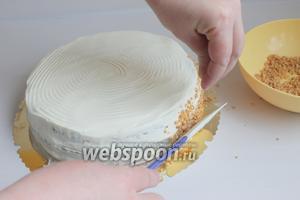 Обсыпаем бока торта. У меня орехи обжаренные. Для этого ставим наискосок лопатку к торту и сыплем наше украшение, затем лопаткой прижимаем.