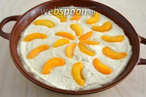 Выложите тесто в смазанную маслом форму диаметром около 26 см, сверху выложите порезанные на ломтики персики.