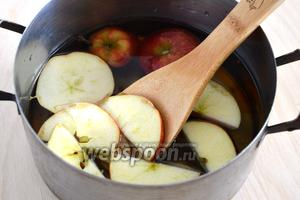 Влейте воду в ковш. Добавьте ломтики яблок, сахар и специи.