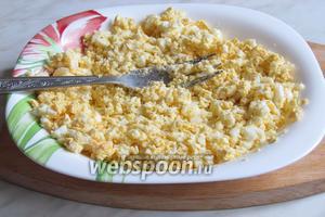 Сваренные вкрутую яйца размять вилкой.