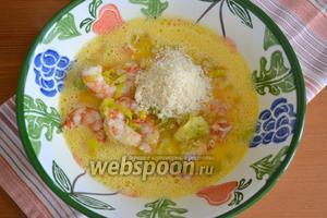 Добавить к яйцам креветки с луком-пореем. Затем добавить тёртый сыр Пармезан. Перемешать.