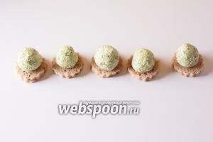 Достаём из морозилки зелёную массу (телесного цвета пока оставляем). Делим её на 5 более или менее одинаковых частей, скатываем шарики и размещаем их по центру хлебных основ для канапе.