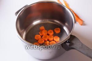 Морковь почистить и порезать крупными шайбами, положить в кастрюлю.