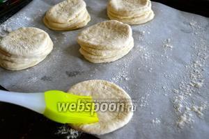 Выложить на противень, застеленный пекарской бумагой булочки, складывая друг на друга кружки, предварительно смазав каждый из них сверху водой. Каждая булочка состоит из 4 кружков.