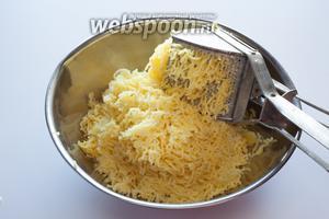 Почистите картошку и продавите её через картофельный пресс (или измельчите любым иным удобным вам способом).