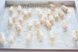 Обваляйте картофельные колбаски в муке. Уже поставьте на разогрев фритюрницу, 2 литра масла до 170-180°С греются довольно долго. Если делаете в небольшом количестве масла — можно подождать.