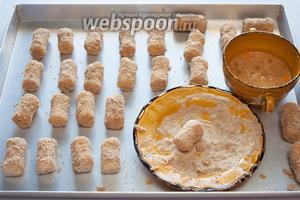 Обмакивайте обвалянные в муке колбаски в разболтанное яйцо и обваливайте их в панировочных сухарях со всех сторон, и с торцов тоже.