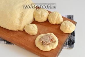 Отрезать от теста кусочки величиной с мандарин. Формировать лепёшку. На середину выкладывать начинку и формировать пирожки.