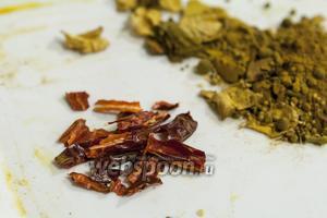 После того, как специи остынут, достанем острые красные перчики и извлечём из них семена, разрезав вдоль ножницами. Очищенные перцы порезать на несколько частей.