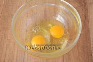 В миску разбиваем куриные яйца, добавляем соль и сахар. Взбиваем венчиком в пышную массу.