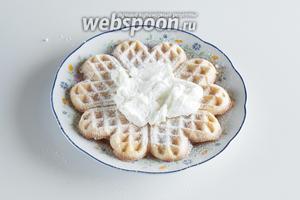 Вафля посыпается сахарной пудрой, намазывается 2-3 ложками взбитых сливок.