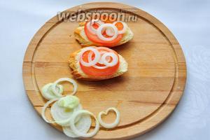 Начинаем собирать наши бутерброды: на каждый кусочек багета кладём 1 кружок помидора, сверху красиво выкладываем луковые кружочки!