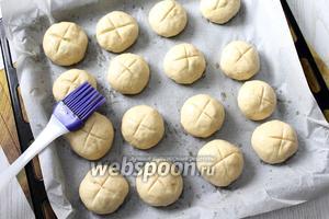 Сделать на булочках надрезы. Смазать сладким чаем, оставить в тёплом месте для расстойки на 20-25 минут.