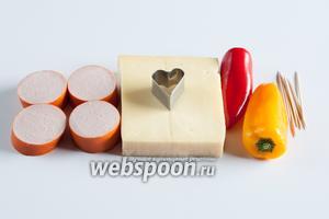 Нам нужны сыр без дыр и колбаса с гомогенной структурой, нарезанная пластами примерно одинаковой толщины (около 1 см), перец паприка 2 разных цветов, зубочистки по количеству планируемых канапе и формочка для вырезания.