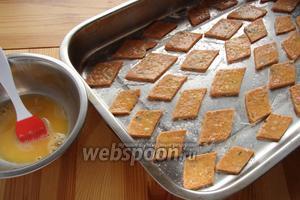 Хорошо тесто накалываем вилкой, нарезаем на ромбики, квадратики, кому как нравится, отправляем на противень, смазываем верх взбитым яйцом и присыпаем солью.