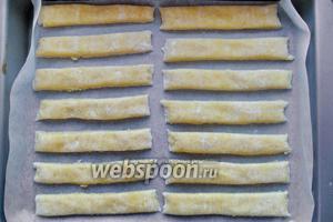 Тесто разрезаем полосками по 1,5 см. Выкладываем наше печенье на пекарскую бумагу. И отправляем в холодильник на 0,5 часа.