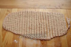 Наше тесто выгружаем на стол, присыпанный мукой, и раскатываем в пласт, толщиной в 0,5 см. На нашу лепёшку распределяем семена кунжута, затем берём нож и нарезаем полоски, толщиной в 1 см.