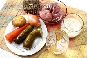 Для приготовления возьмите воду, картофель, рис, морковь, лук репчатый, масло растительное, мясо, соль, огурцы солёные и лавровый лист.
