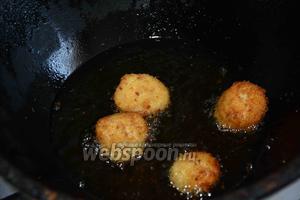 В казане раскалить подсолнечное масло. В раскалённое масло выложить шарики, обжарить до золотистого цвета.